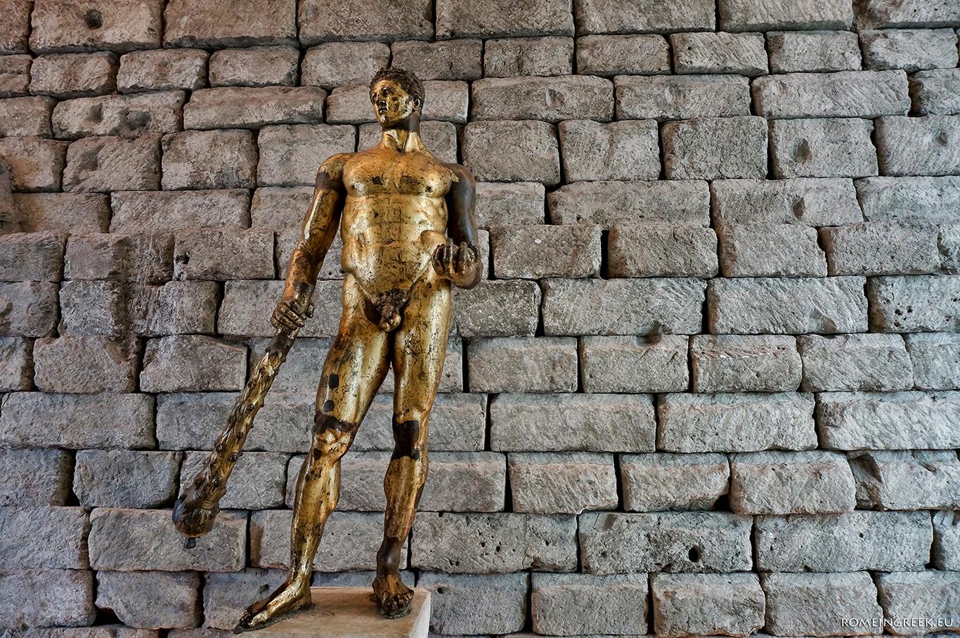 Το άγαλμα του Ηρακλή με φόντο τα θεμέλια του ναού του Δία
