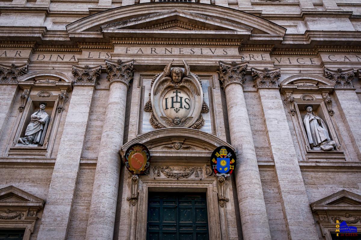 Η είσοδος, με το έμβλημα των Ιησουιτών: Tο χριστόγραμμα IHS του «Ιησούς», με σταυρό και τρία καρφιά.