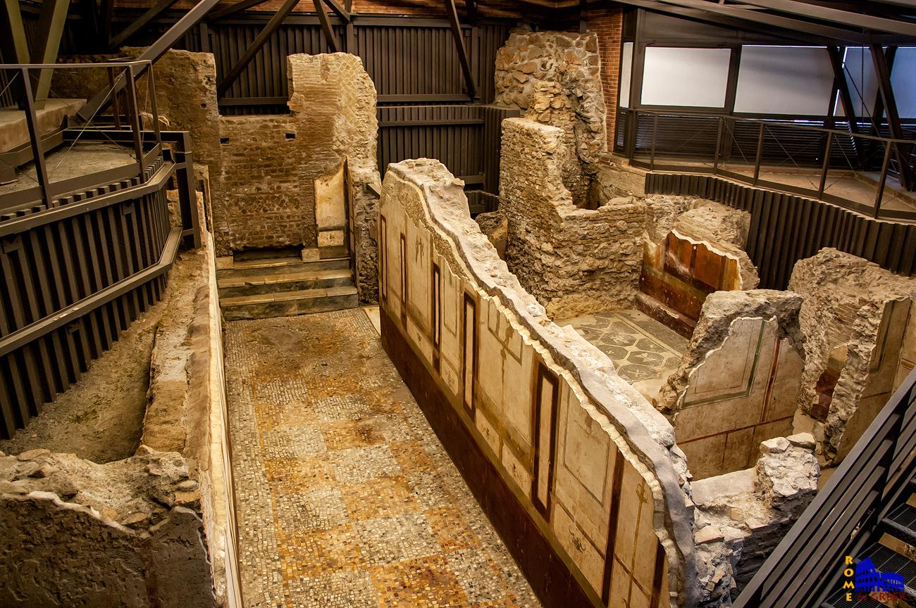 Ένας κεντρικός διάδρομος με μωσαϊκό από μάρματο. Στο βάθος σκαλοπάτια οδηγούν σε κάποιο άλλο χώρο που κλείστηκε με τοίχο σε μεταγενεστερη εποχή.