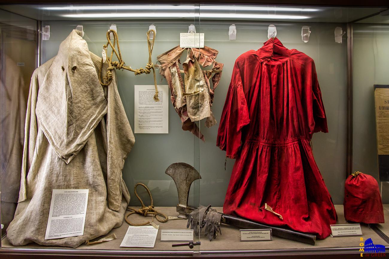 Αριστερά: μανδύας και κουκούλα παρηγορητή. Εμφάνιση κάθε άλλο παρά καθυσηχαστική. Δεξιά: Ενδυμασία δημίου με τσεκούρι αποκεφαλισμού. (Ρώμη, Εγκληματικό Μουσείο)