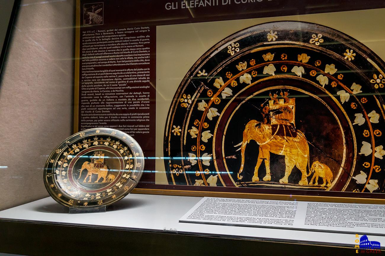 Το 275 π.Χ. ο ύπατος Κούριος Δεντάτος νίκησε τον Πύρρο στο Beneventum της Ιταλίας. Στην μάχη έπεσαν ζωντανοί στα χέρια των Ρωμαίων 8 πολεμικοί ελέφαντες. Τέσσερις από αυτούς παρέλασαν κατά την θριαμβευτική επιστροφή στην Ρώμη. Μια μαρτυρία αυτής της παρέλασης είναι το πιάτο που βρέθηκε στην Capena, μέρος μάλλον μιας ολόκληρης σειράς.