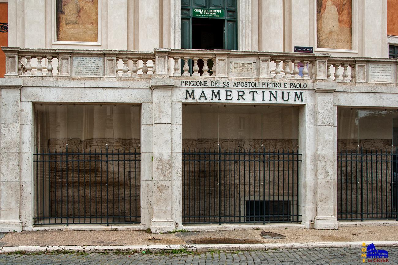 Η είσοδος των φυλακών. Πίσω από το προστατευτικό τζάμι διακρίνεται η αυθεντική ρωμαϊκή πρόσοψη. Η επιγραφή «C. VIBIUS RUFINUS e M. COCCEIUS NERVA» αναφέρεται στους ύπατους Ρουφίνιο και Νέρβα που επιμελήθηκαν την ανακαίνιση υπό αυτοκρατορίας Τιβέριου.