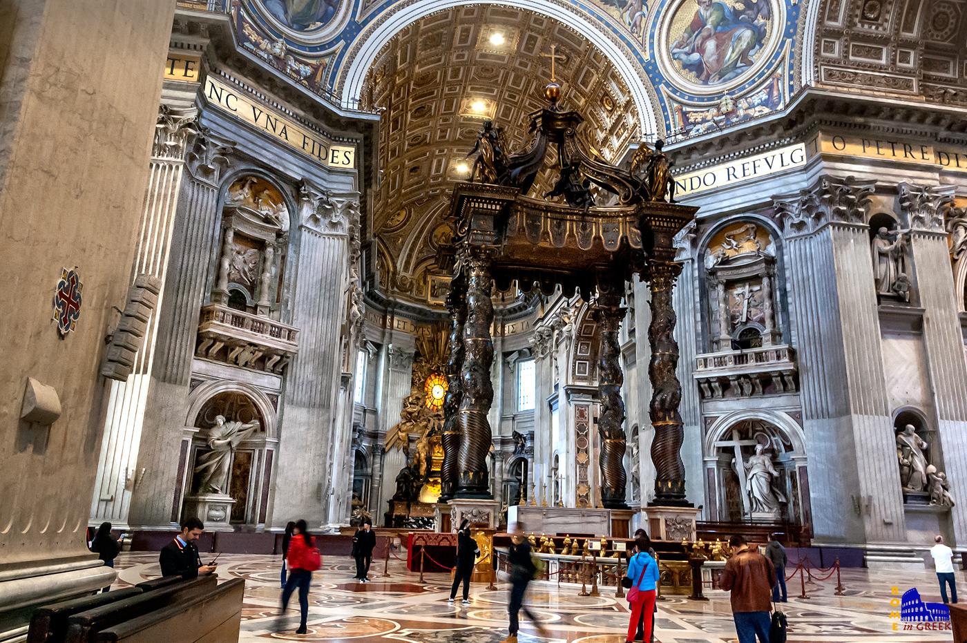 Ο παπικός βωμός με το Ουρανό (Baldacchino) του Μπερνίνι, κατασκευασμένο από χαλκό που αφαιρέθηκε από το Πάνθεον. Αριστερά και δεξιά δύο πυλώνες με άγαλμα στη βάση και μπαλκονάκι. Αριστερά η Αγία Βερονίκη, δεξιά η Αγία Ελένη.