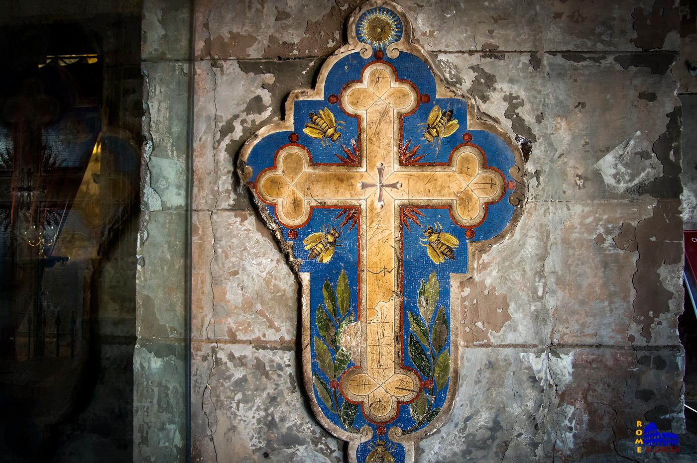 Ο σταυρός του Μπορομίνι. Φιλοτέχνησε ο ίδιος τον σταυρό, ενώ οι διακοσμήσεις στο μπλε φόντο είναι του Giovanni Battista Calandra. Οι μέλισσες και τα φύλλα ελιάς είναι τα σύμβολα των οικογενειών Barberini και Pamphilj, δύο από τις ισχυρότερες της εποχής, όπου είχαν στις τάξεις τους μέχρι και πάπες. Κατά μήκος του περιγράμματος του μωσαϊκού φαίνονται ακόμα τα σημάδια από το σφυρί που χρησιμοποίησε ο Ιννοκέντιος Ι΄κατά το Ιωβηλαίο Έτος του 1649 για να σπάσει τις σφραγίδες που κρατούσαν την Αγία Θύρα κλειστή.